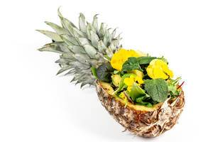 Pineapple stuffed with mix of different lettuce leaves and edible flowers