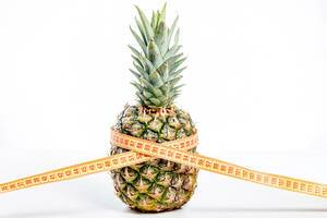 Pineapple with measuring tape on white background. Diet food concept