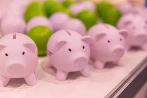 Pink piggy banks and colorful balls in the background