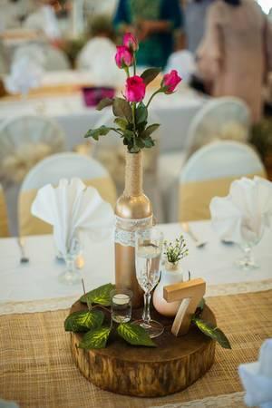 Pinke Rosen in goldener Flasche neben Glas Champagner bildet Tischdekoration bei Hochzeit