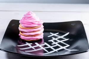 Pinker Nachtisch mit farbiger Sahne auf einem schwarzen, verzierten Teller