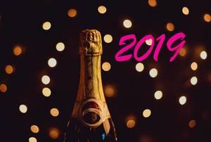 Pinker Schriftzug 2019 neben ungeöffneter Champagnerflasche und Lichteffekten auf dunklem Hintergrund