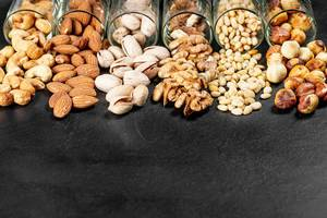Pistachios, almonds, cashews, walnuts, pine nuts and hazelnuts on a black background (Flip 2020)
