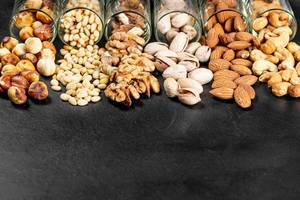 Pistachios, almonds, cashews, walnuts, pine nuts and hazelnuts on a black background