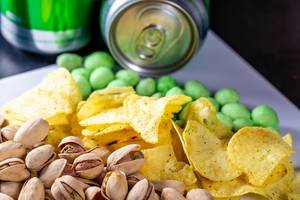 Pistachios, chips and peanuts with a can of beer