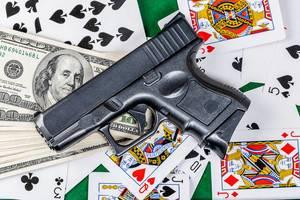 Pistole, amerikanisches Geld und Spielkarten auf einem grünen Pokertisch