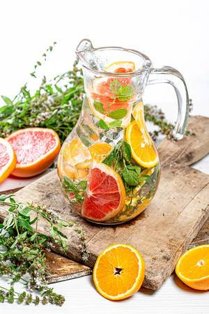 Pitcher of ice cubes, fresh mint, and citrus slices on old kitchen boards