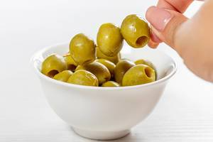 Pitted green olives in bowl on white background (Flip 2019)