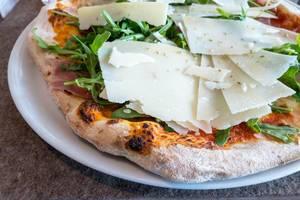 Pizza mit Parmesan, Rucola und Parmaschinken