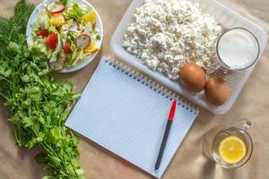 Planning diet concept. Flat lay view of notepad with a pen and organic healthy food: cottage cheese, eggs, greens, salad, apple, and greens on brown paper