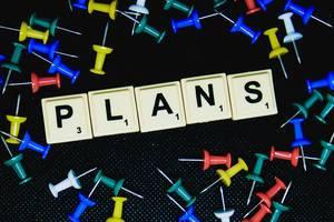 Plans (Pläne) Text mit Reißzwecken auf schwarzem Untergrund