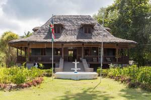 Plantation House National Monument - Sehenswürdigkeit mit Strohdach und weißem Brunnen ist Teil des L
