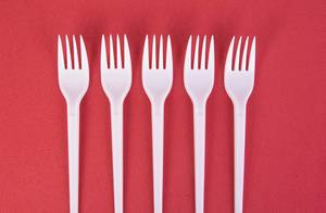 Plastic forks on red background