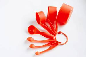 Plastic measuring cups and spoons on white background.