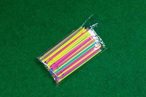Plastik-Trinkhalme in Plastikverpackung auf grünem Hintergrund
