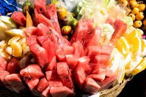 Plastikbeutel mit verschiedenen geschnittenen Früchten wie Wassermelone oder Mandarinen in Korb