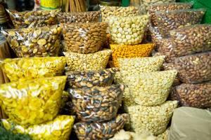 Plastikbeutel mit verschiedenen, in Plastikbeuteln abgepackten Kernen, Nüssen und Samen an einem Marktstand