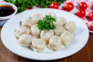 Plate of dumplings with sauce, herbs and cherry tomatoes