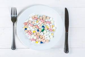 Plate with different pills and capsules on a white wooden table with a fork and a knife
