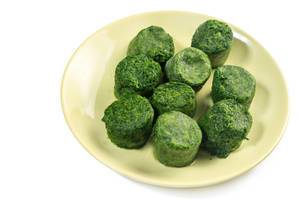 Plate with Frozen cubes of Spinach above white background