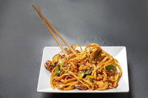 Plate with rice noodles and chopsticks on black background (Flip 2019)