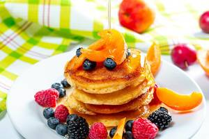 Plate with tasty pancakes and berries, honey pours from the top (Flip 2019)