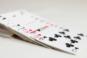 Playing cards slided from a deck close up on a white background