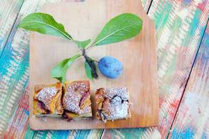 Plum cakes with fresh plum fruit on a wooden background (Flip 2019)