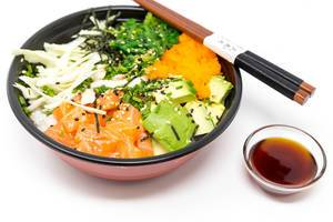 Poke Bowl Salmon Teriyaki  - with sushi rice, salmon, avocado, cabbage, wakame, wasago, nori, teriyaki-sauce, soy-sauce, sesame and chives in a bowl with chopsticks