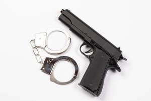 Polizei-Ausrüstung - Schwarze Handfeuerwaffe neben Handschellen vor weißem Hintergrund