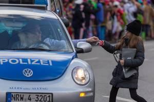 Polizeibeamter gibt einem Mädchen einen Lutscher - Kölner Karneval 2018