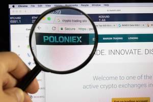 Poloniex-Logo am PC-Monitor, durch eine Lupe fotografiert