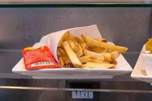 Pommes mit Ketchup-Tütchen auf einem Teller