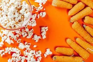 Popcorn and raw corn on orange background