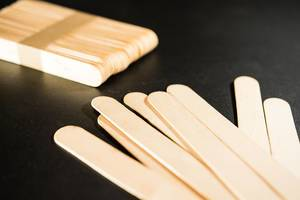 Popsicle craft sticks on a black surface