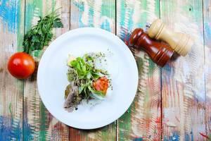 Pork steak with fresh tomato in white plate. Wooden vintage background (Flip 2019)