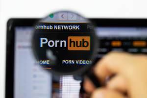 Pornhub-Logo am PC-Monitor, durch eine Lupe fotografiert