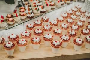 Portionen an Panna Cotta mit Erdbeeren und Sahnehäubchen in Plastikbecher