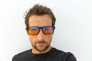 Portrait of a man wearing Horus X blue light blocking glasses for gamers, on a white background
