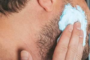 Portrait of male putting shaving foam on his beard. Skin care concept (Flip 2019)