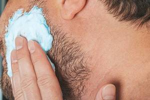 Portrait of male putting shaving foam on his beard. Skin care concept