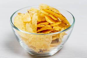 Potato chips in a glass bowl on a white table