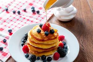 Pouring honey onto tasty pancakes with berries on table, closeup