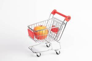 Praller, roter Apfel in Einkaufswagen vor weißem Hintergrund