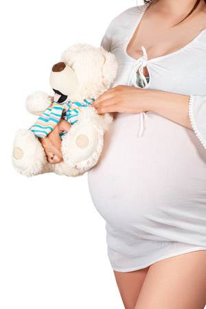 Pregnant girl hugs bear soft toy