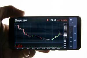 Preisentwicklung des Ethereum Index auf Display eines Mobiltelefons in der Hand eines Mannes