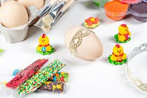 Preparing for the Easter holiday- eggs, decor and paints on white background (Flip 2020)