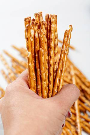 Pretzel sticks close-up in a woman