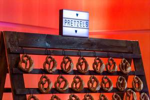 Pretzels on display: traditional German food on a wooden stand with lit sign