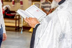 Priest holding a Bible in hands (Flip 2019)